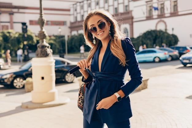 Elegancka atrakcyjna kobieta ubrana w niebieski stylowy garnitur i okulary przeciwsłoneczne, chodzenie na ulicy trzymając torebkę