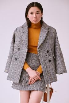 Elegancka azjatka w modnym wełnianym płaszczu i klasycznej spódnicy
