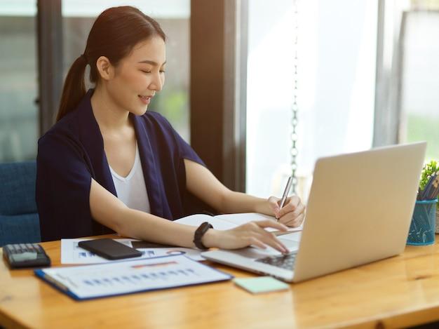 Elegancka azjatycka kobieta siedzi w biurze, pracuje na laptopie i robi notatki na notebooku, analityk biznesowy pracujący w biurze
