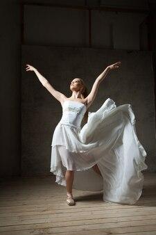 Elegancka balerina w białym tańcu z rozpostartymi ramionami i latającą spódniczką w studio