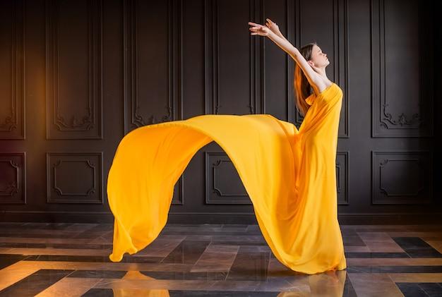 Elegancka balerina w pointe tańczy na ciemnoszarym tle z powiewną żółtą tkaniną