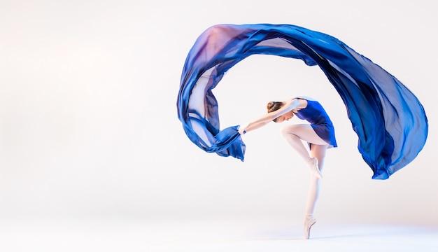 Elegancka balerina w pointes tańczy z rozwijającym się niebieskim suknem