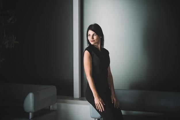 Elegancka biznesowa dama siedzi w holu urzędu. zdjęcie z kopią przestrzeni
