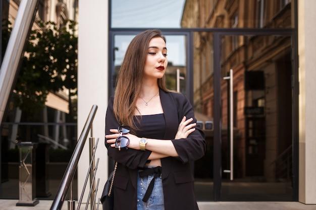Elegancka biznesowa dama w kurtce z szkłami w rękach na tle budynek biurowy