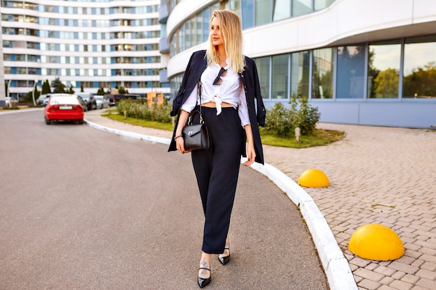 Elegancka bizneswoman pozuje na ulicy w pobliżu biura, ubrana w modny stylowy garnitur i skórzaną torbę, blond włosy. pełnej długości portret modnej modelki.