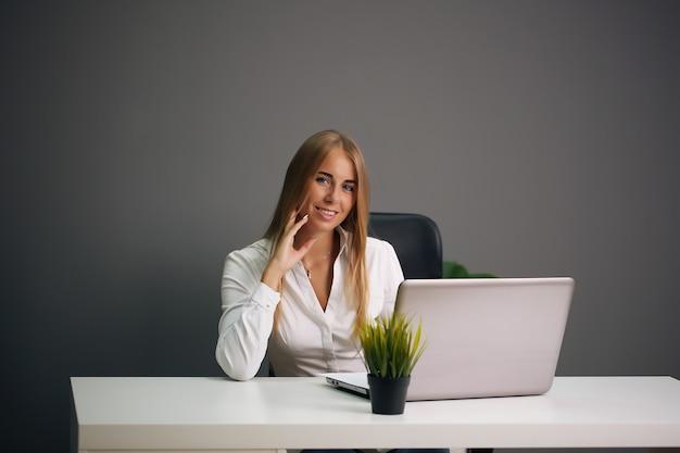 Elegancka bizneswoman siedzi w swoim biurze