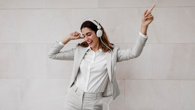 Elegancka bizneswoman, słuchanie muzyki na słuchawkach