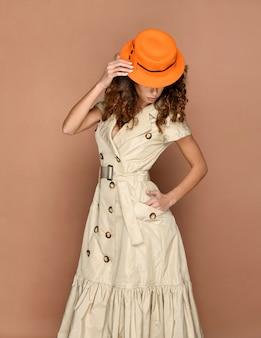 Elegancka bizneswoman w modzie metropolitalnej ubrana w stylowy pomarańczowy kapelusz i kremową sukienkę pozowanie patrząc w dół na brązowej ścianie