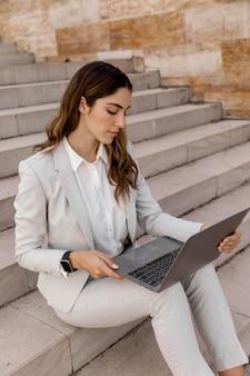 Elegancka bizneswoman z smartwatch pracuje na laptopie siedząc na schodach