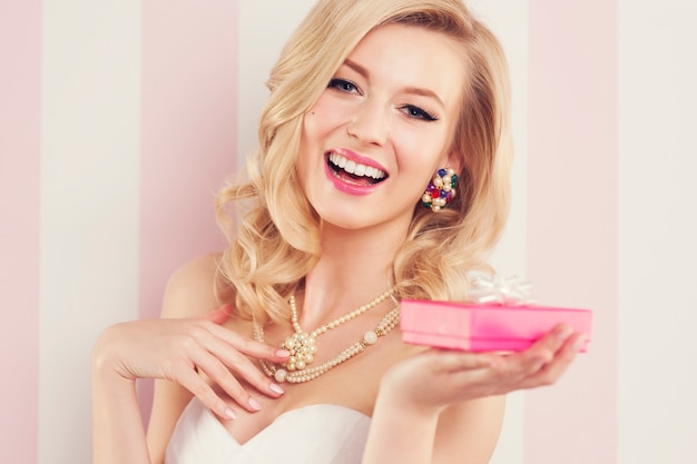 Elegancka blond kobieta trzyma różowy prezent