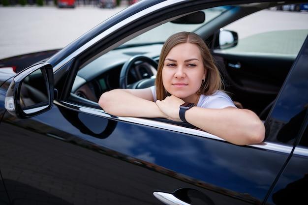 Elegancka blondynka piękna kobieta siedzi w luksusowym samochodzie. niezależna kobieta biznesmen koncepcja