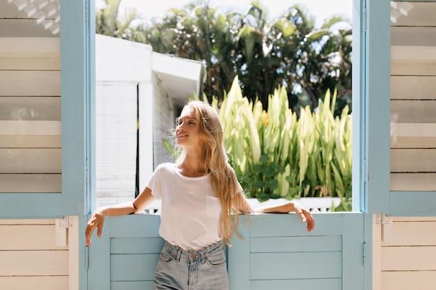 Elegancka blondynka pozuje z zamkniętymi oczami i natchniony uśmiechem. zdjęcie szczupłej uroczej kobiety z długimi włosami.
