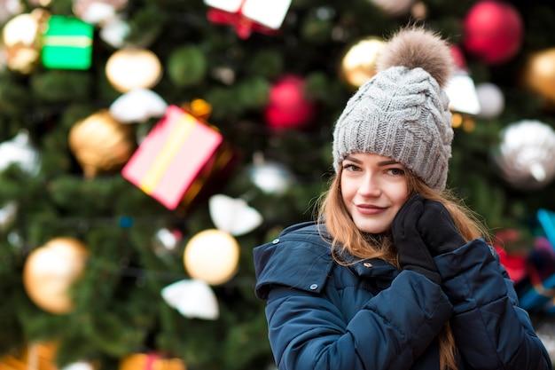 Elegancka blondynka w ciepłym kapeluszu z dzianiny pozuje na świerkowym tle