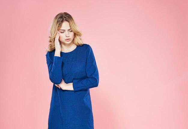 Elegancka blondynka w niebieskiej sukience emocje styl życia studio luksusowe różowe tło