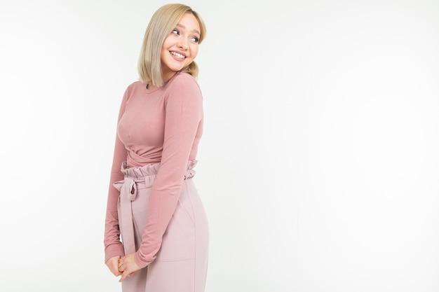 Elegancka blondynki dziewczyna w różowej bluzce pozuje na bielu z kopii przestrzenią