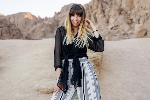 Elegancka brunetka kobieta pozowanie na wydmach egipskiej pustyni.