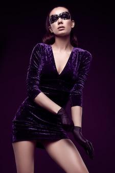 Elegancka brunetka kobieta w pięknej fioletowej sukience i cekinami maska rękawiczki