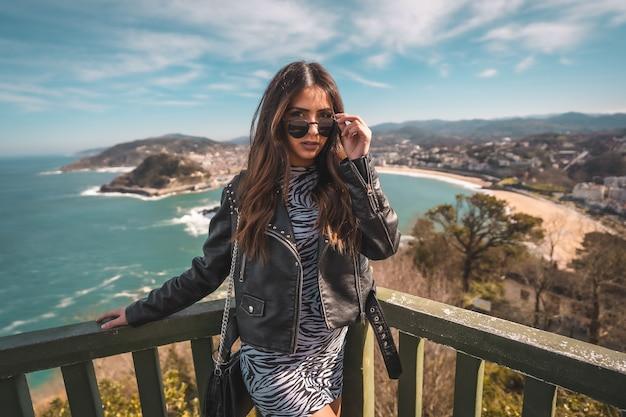 Elegancka brunetka modelka z okularami przeciwsłonecznymi na punkcie widokowym w san sebastian, hiszpania