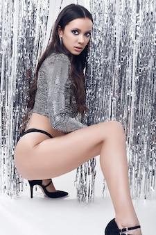 Elegancka brunetka z idealnym ciałem w luksusowym cekinowym topie
