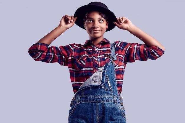Elegancka czarna hipster dziewczyna z krótkimi włosami w kraciastą koszulę i jeansowy kombinezon.