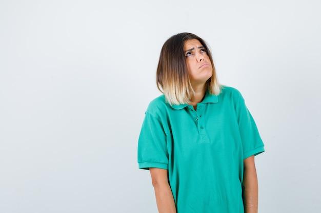 Elegancka dama patrząca w górę w koszulce polo i wyglądająca na niezorientowaną. przedni widok.