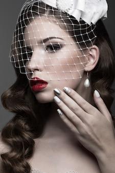 Elegancka dama w futrze z welonem i wzorem paznokci. obraz zimowy. zdjęcie zrobione w studio na szarym tle. piękna twarz.