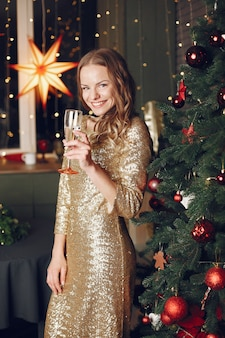 Elegancka dama w pobliżu choinki. kobieta w domu z szampanem.