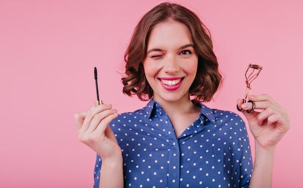 Elegancka dama z krótką fryzurą robi rzęsy i śmieje się. kryty zdjęcie uśmiechniętej kręconej kobiety trzymającej tusz do rzęs na różowej ścianie.