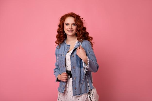 Elegancka dziewczyna imbir patrząc na kamery z torebką. strzał studio uśmiechnięta romantyczna dama w dżinsowej kurtce na białym tle na różowym tle.