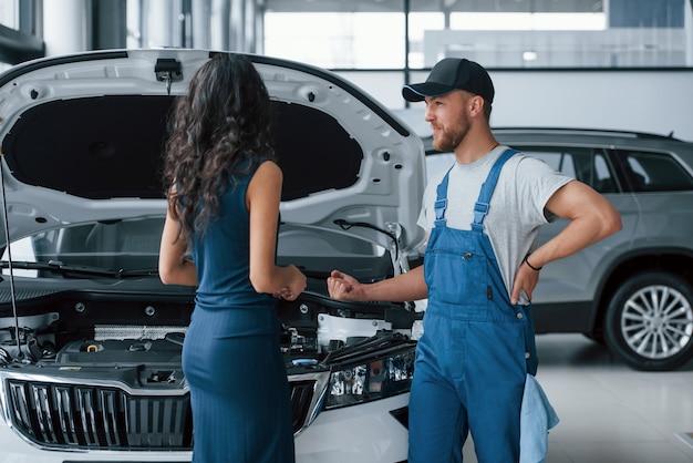 Elegancka dziewczyna. kobieta w salonie samochodowym z pracownikiem w niebieskim mundurze, odbierając jej naprawiony samochód