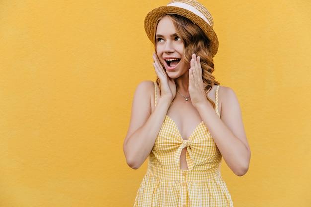 Elegancka dziewczyna nosi słomkowy kapelusz i naszyjnik z zaskoczonym uśmiechem. zdziwiona kręcona kobieta w żółtej sukience stojącej.