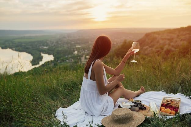 Elegancka dziewczyna odpoczywa na wzgórzu na letni piknik o zachodzie słońca.