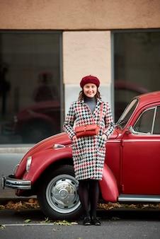 Elegancka dziewczyna pozuje blisko czerwonego retro samochodu. na zewnątrz, jesienne miasto