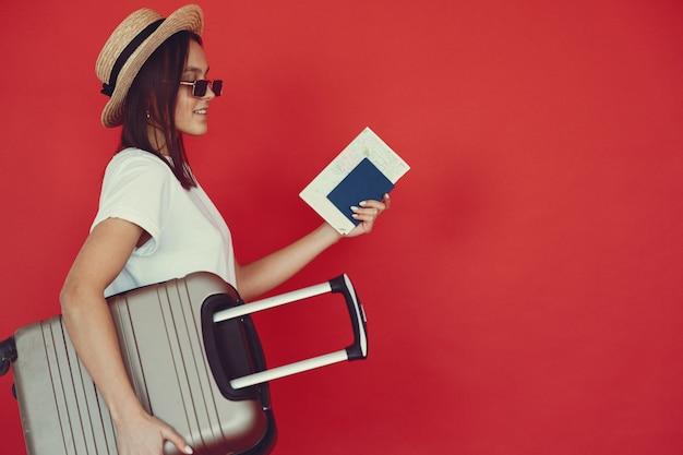 Elegancka dziewczyna pozuje z podróży wyposażeniem na czerwonej ścianie