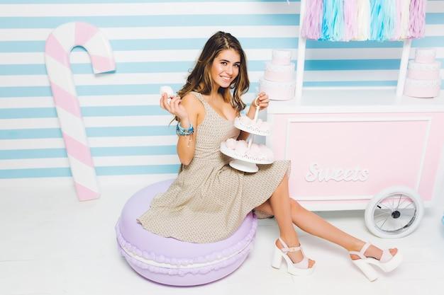 Elegancka dziewczyna pracuje w sklepie ze słodyczami, trzymając smaczne ciasteczka i uśmiechając się z wyrazem zadowolonej twarzy. marzycielska młoda kobieta w sukienka vintage siedzi z pysznym deserem w pobliżu kontuaru z ciastami.
