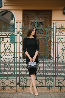 Elegancka dziewczyna w czarnej sukience trzyma w dłoniach torbę i stoi przy bramie z kutego żelaza w domu