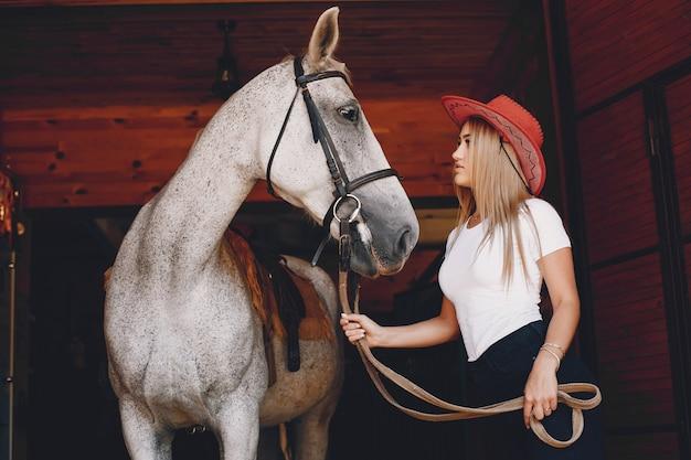 Elegancka dziewczyna w gospodarstwie wiith konia