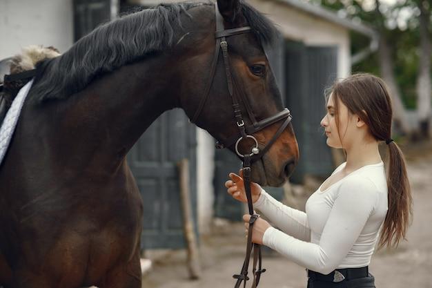 Elegancka dziewczyna w gospodarstwie z koniem