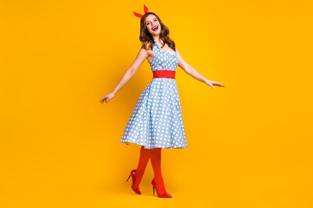 Elegancka dziewczyna w sukience w kropki czerwony pentyhose spacer na żółtym tle
