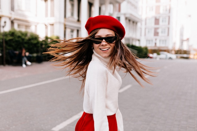 Elegancka dziewczyna z długimi włosami śmiejąc się podczas zwiedzania nowoczesnej części miasta.