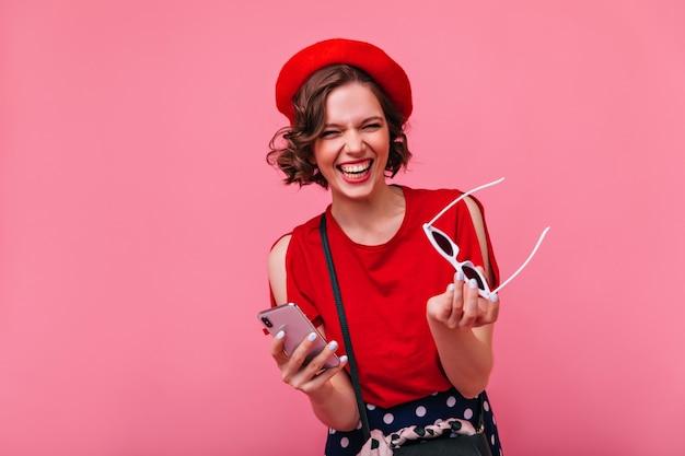 Elegancka francuska dziewczyna trzyma w ręku okulary przeciwsłoneczne i uśmiecha się. cieszę się, że ciemnowłosa kobieta w czerwonym stroju się śmieje.