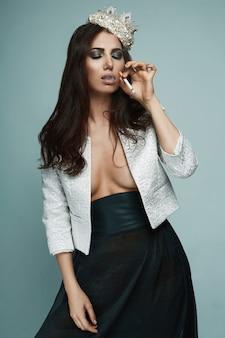 Elegancka gorąca brunetka kobieta w złotej koronie pali papierosa na czarnym tle w studio