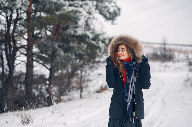 Elegancka i młoda dziewczyna w zima parku