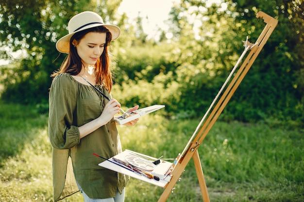 Elegancka i piękna dziewczyna maluje w polu