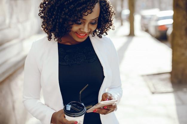 Elegancka i stylowa ciemnoskóra dziewczyna o kręconych włosach i chodzącej białej kurtce