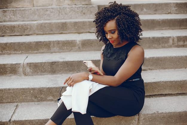 Elegancka i stylowa ciemnoskóra dziewczyna o kręconych włosach i siedzącej białej marynarce