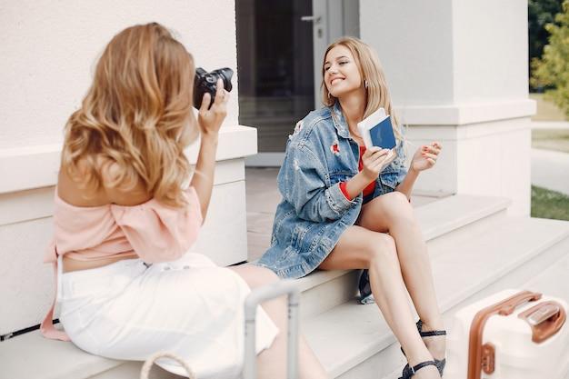 Elegancka i stylowa dziewczyna siedząca z walizką