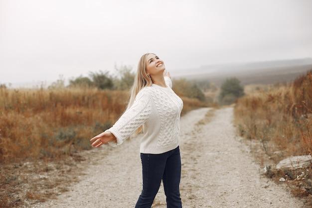 Elegancka i stylowa dziewczyna w jesiennych polach
