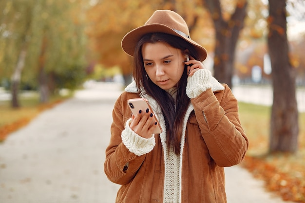Elegancka i stylowa dziewczyna w jesiennym parku