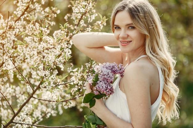 Elegancka i stylowa dziewczyna w wiosennym parku